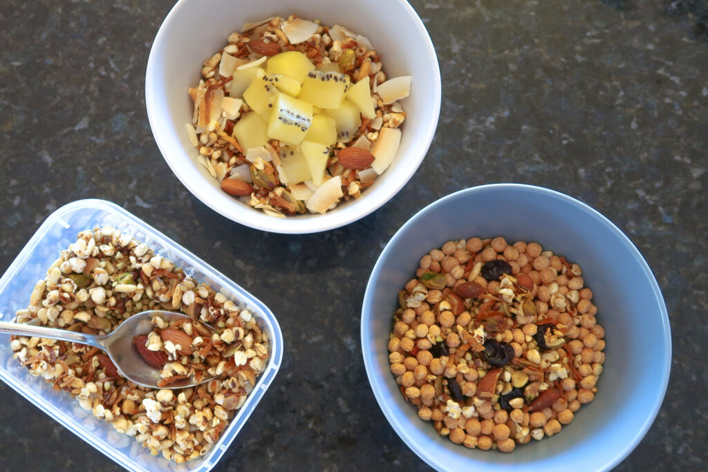 Two bowls of granola, one with kiwi and coconut and the other with dried cherries and protein crunch cereal.  container of the Granola base recipe is to the side.