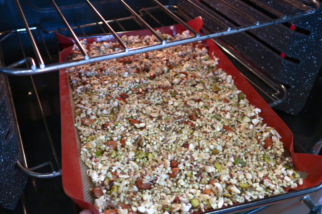 Granola tray partially in the oven.